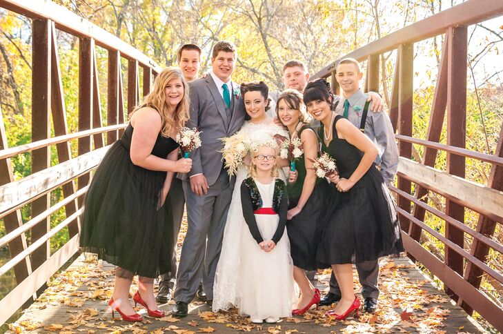 Leah's bridesmaids wore pin-up-inspired black dresses with red peep-toes to fit the retro wedding theme, while the groomsmen wore shirts and suspenders with bright teal ties. The flower girl wore a traditional white tulle dress with a bright red sash and a black sparkly bolero that resembled a retro leather jacket.