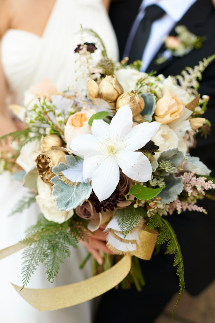 "The bride's stepsister and owner of Asrai Garden in Chicago created this gold-dipped bouquet. ""She generously offered to do the flowers -- creating them in Chicago and driving them to Minneapolis,"" Jodi says. ""She created this stunning bouquet filled with gold-dipped flowers and feathers."""