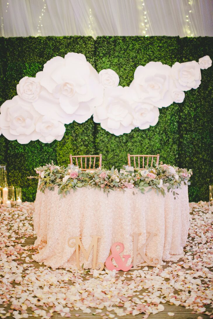 Marisa and Kyle sat at their sweetheart table draped with a lush garland, filled with romantic blooms and greenery. Pink cherry blossom petals surrounded the table, positioned in front of a large gardenia wall decoration on a trimmed hedge backdrop.