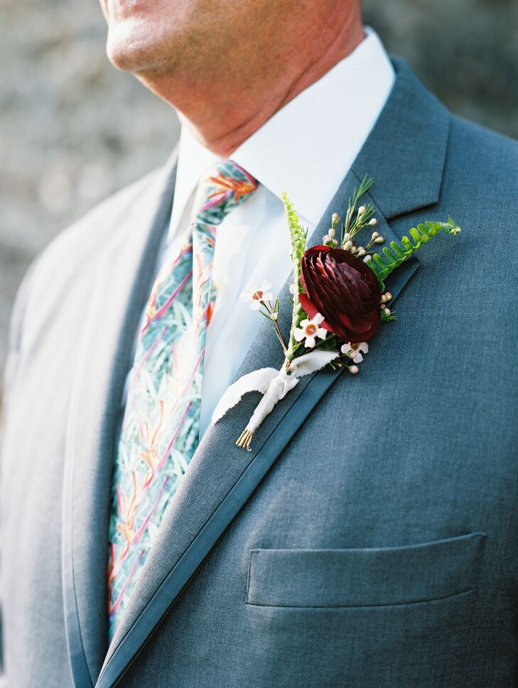 Boutonnieres were crafted with delicate fern sprigs and a single deep burgundy blossom.