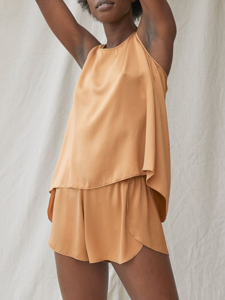 Woman wearing silk pajama shorts and tank top set in marigold