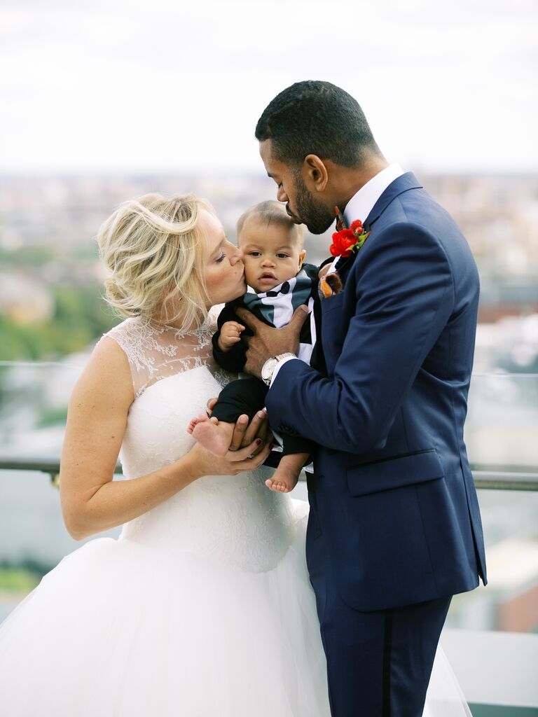 Couple kissing baby