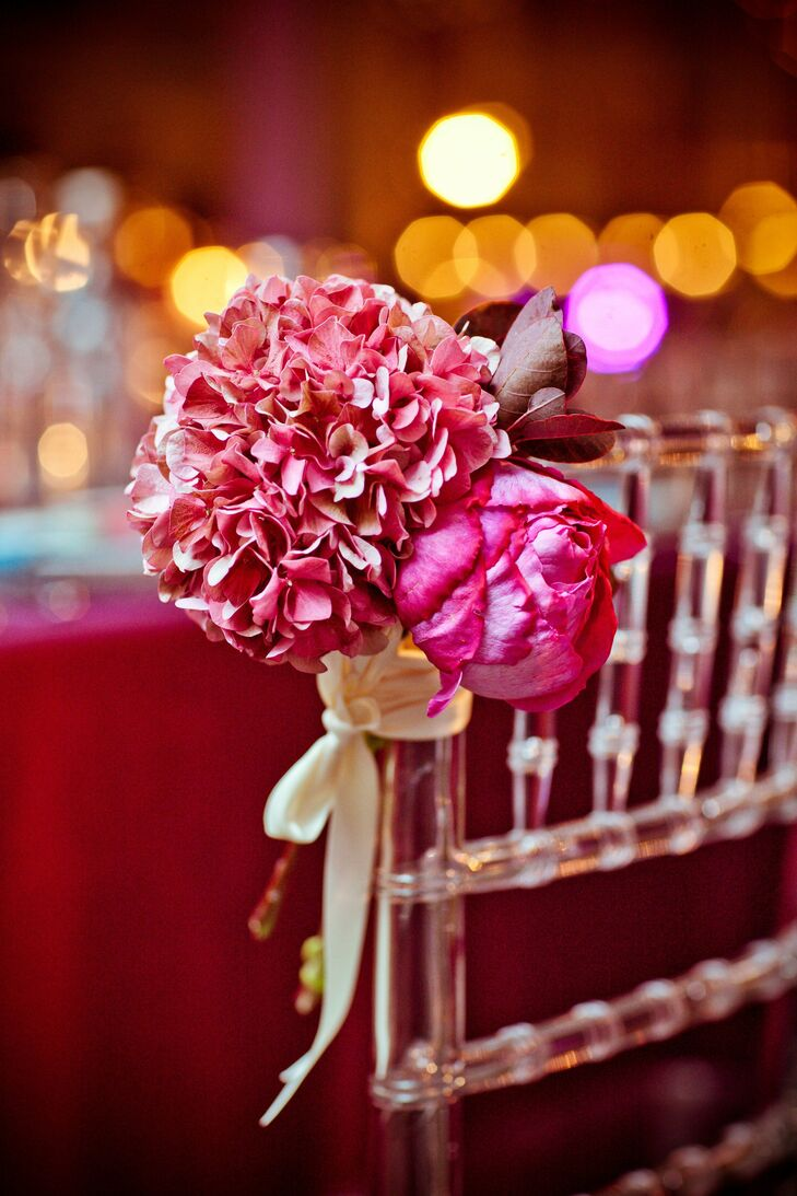 Pink hydrangea and peonies were tied to the ceremony chairs with ivory ribbon.