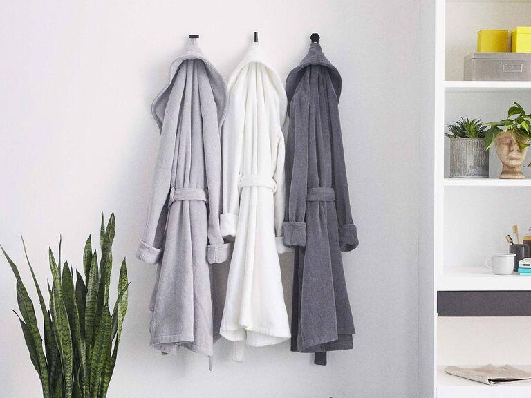 Three plush bath robes in light gray, white, and dark gray hanging on hooks