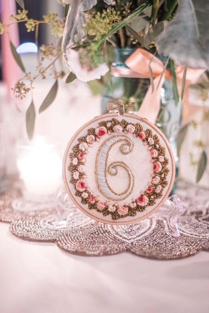 "Taking inspiration from the centerpiece florals, Kelly created and embroidered delicate table numbers. ""We are very DIY, if you hadn't guessed!"" she said."