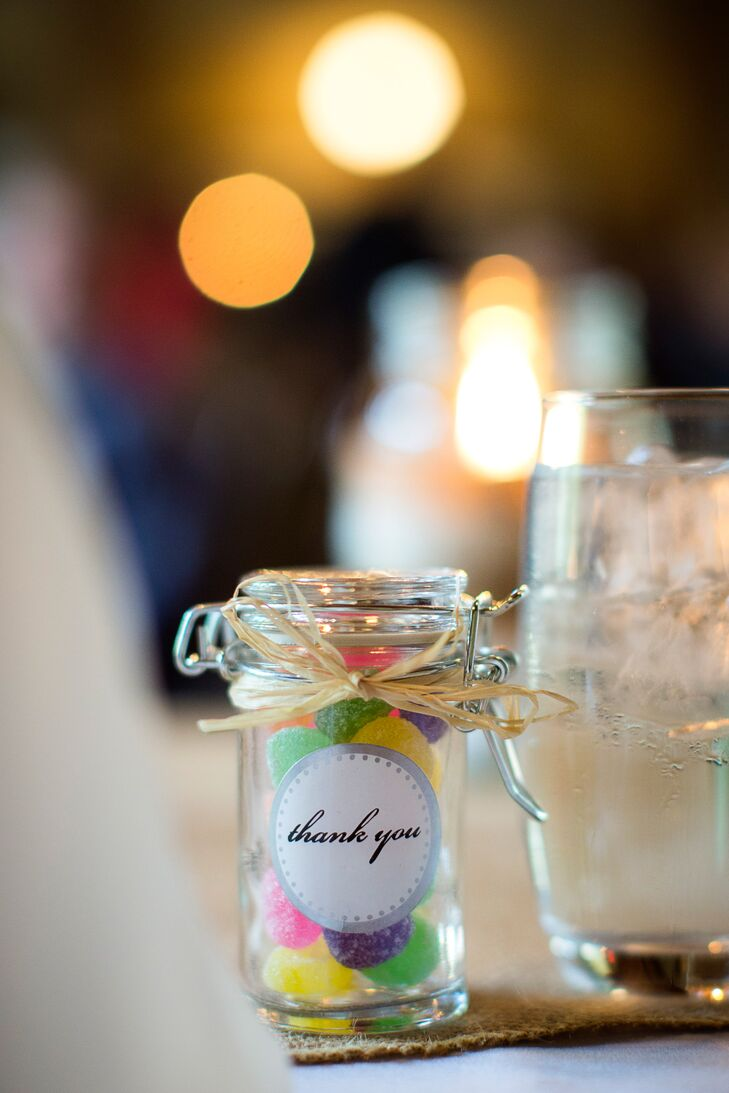 A small glass jar filled with colorful gummy candies were given out to guests as favors.