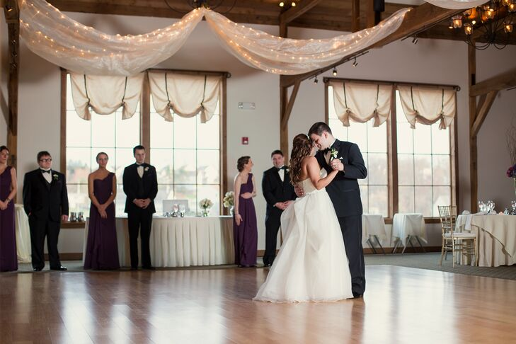 """Sarah and Matt added a few fun accents to their reception with white fabric draped along the ceiling, which was covered in string lighting. Each white linen-covered table was also met with a fun hydrangea centerpiece. """"The place even had a patio. We had a fire pit there where people could get warm and make s'mores,"""" Sarah says."""