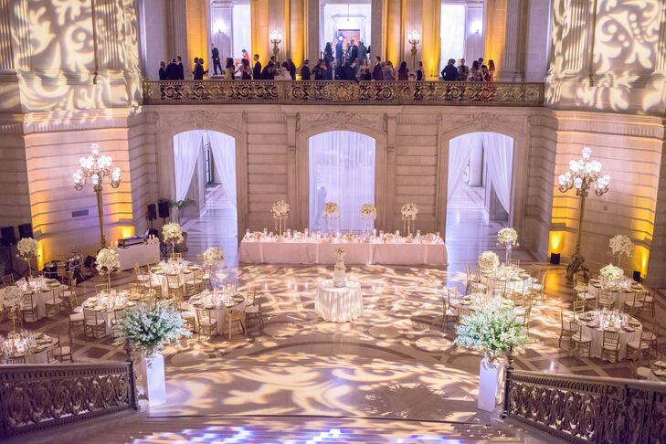 To fit to the space's grand architectural details, Beth and Eric played with light to transform the room into a romantic dinner party. The couple even projected their custom monogram on the staircase during the reception.
