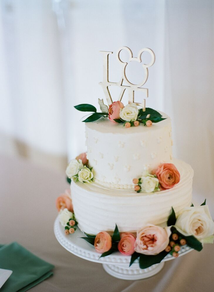 """Jamie and Alex's whimsical """"love"""" cake topper incorporated Mickey Mouse and a cat. """"We love our cat, and he has really made us feel like a family the last two years,"""" Jamie says. """"We couldn't take him to Maine with us but wanted him represented at the wedding."""""""