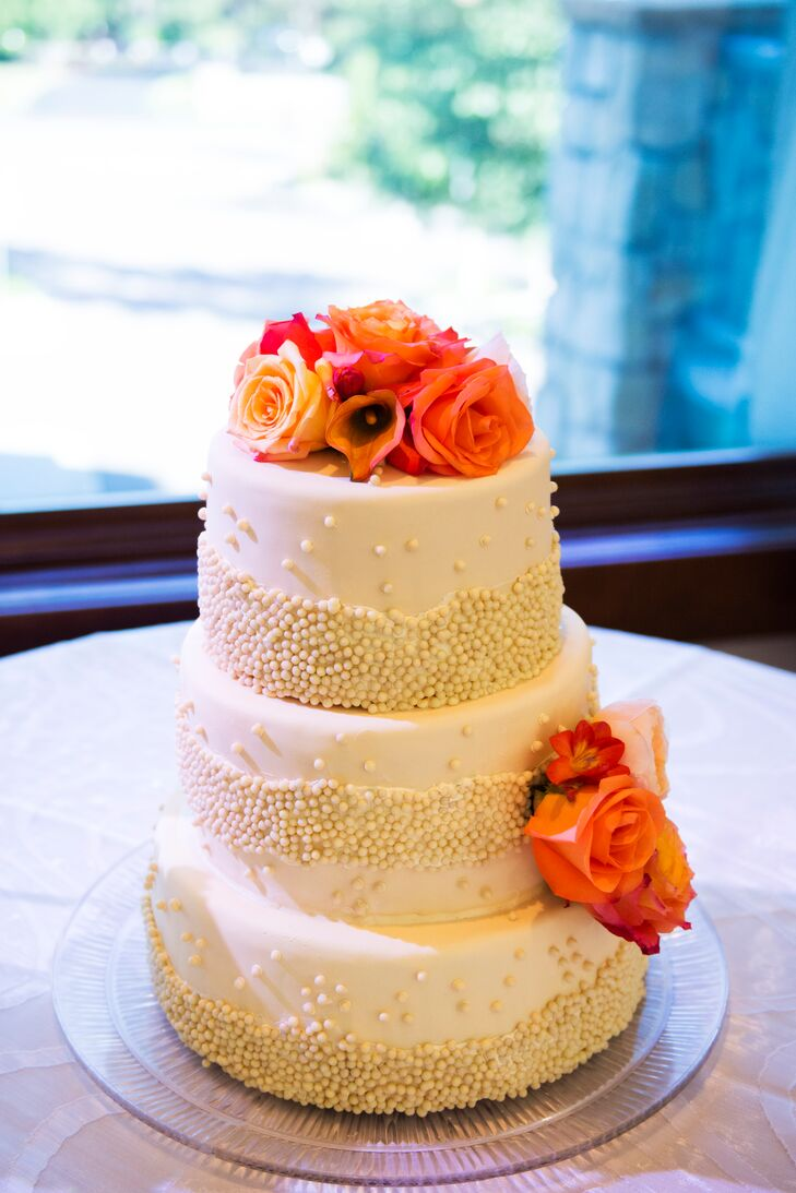 Cara and Josh enjoyed a three-tier white fondant wedding cake decorated with ivory beadeds and topped with orange roses and calla lilies.