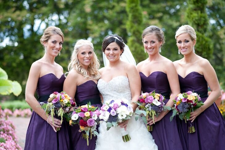 The bridesmaids wore Jim Hjlem A-line ballgowns with a sweetheart neckline in eggplant.The bride chose to have a bouquet of whites, creams and various shades of purple, while selecting jewel tones for her bridesmaids.