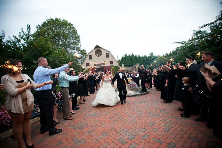 Guests line the brick pathway holding out sparklers to welcome the bride and groom to the reception. The sparklers were a fun surprise twist to an elegant, traditional theme.