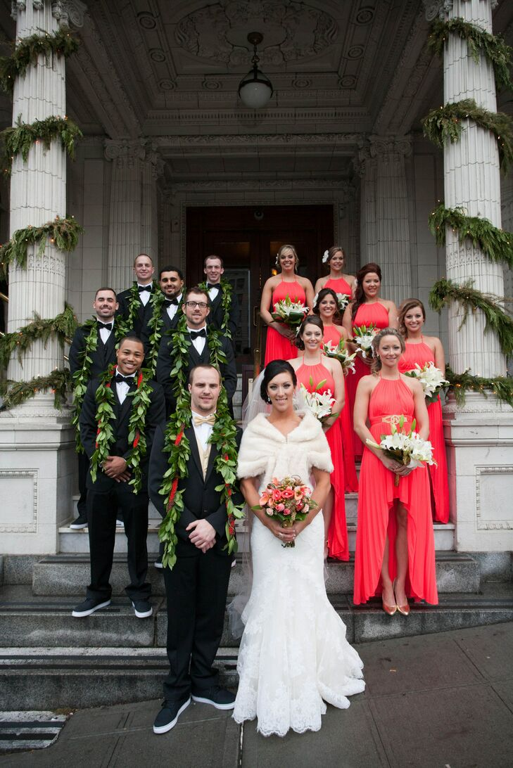 Shantelle and Alex stood on the steps of their venue with the entire wedding party behind them. The groom and his groomsmen wore classic black tuxedos draped with traditional leis from the ceremony, and the bridesmaids wore coral long bridesmaid dresses.