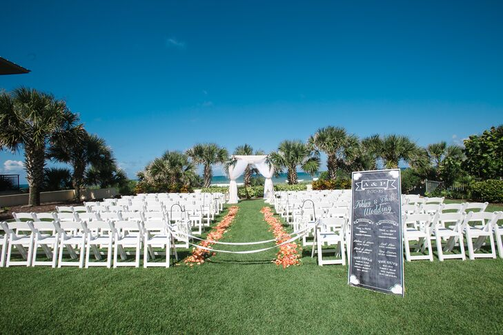 """Ashley and Phil loved the idea of a beach-chic wedding. So they took advantage of the Hammock Beach Resort's waterfront ceremony space in Palm Coast, Florida, and highlighted the entire setting with white and orange decor. Orange and white flower petals lined rows of white folding chairs toward the beach. A chalkboard wedding program also marked the front. """"The chalkboard sign was very special,"""" Ashley says. """"It will hang in our new house this fall."""""""