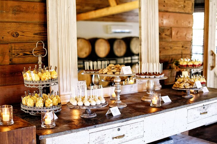 In addition to the wedding cake, the couple also had a dessert table to show their love for sweets. The desserts, which ranged from cake balls to cheesecake shooters and cookies, were displayed on a rustic wooden table at the reception.