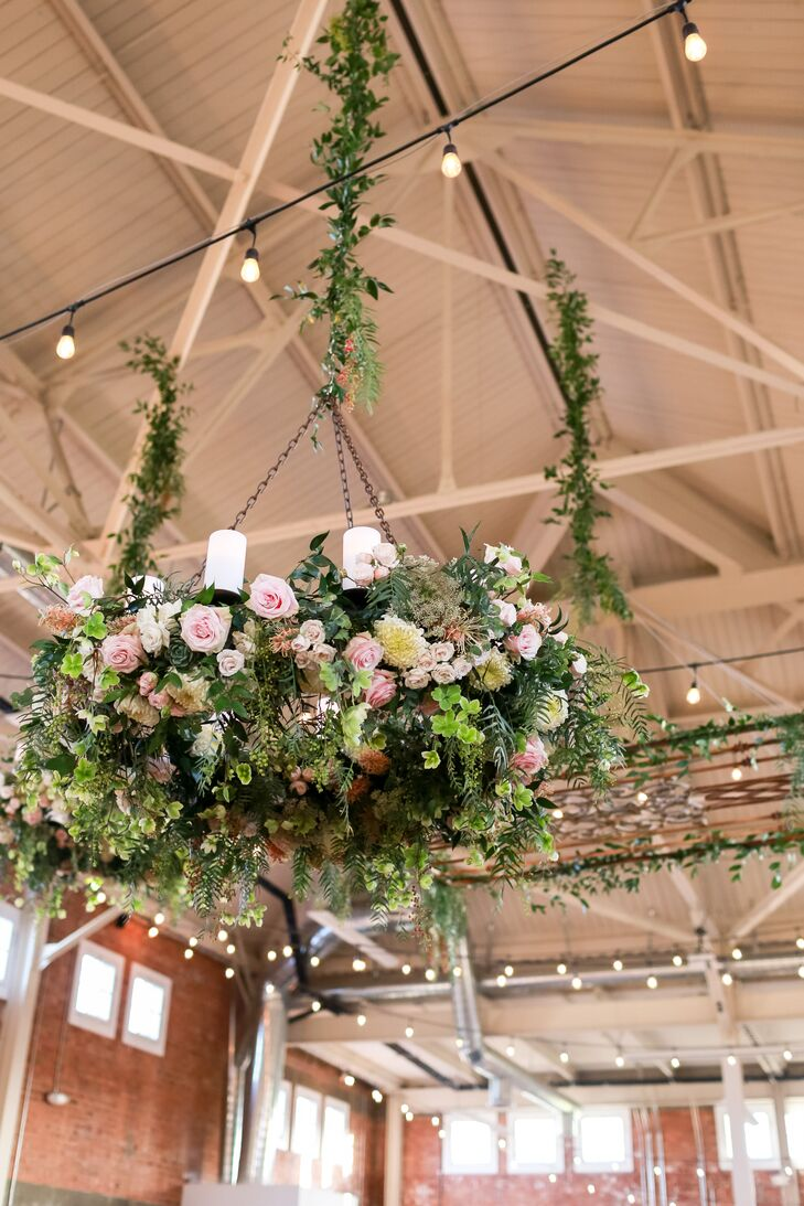 """Our florist created beautiful chandeliers covered in greenery that owned the room,"" Andrea says of florist Flowers Annette Gomez. ""She also took a vintage gate, put minimal greenery on the edges and hung that from the ceiling as well, which was such an exciting element."""