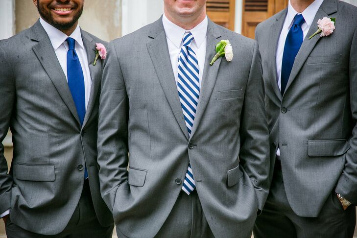 Brian and his groomsmen paired gray suits with black leather dress shoes and a ranunculus boutonniere. The groomsmen wore solid navy ties while Brian wore a navy-and-white-striped tie to keep with the nautical motif.