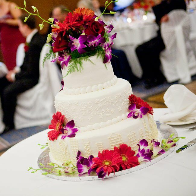 Talk about glam! Rich red flowers cascaded down the three-tiered cake iced decorated with a custom-monogram.