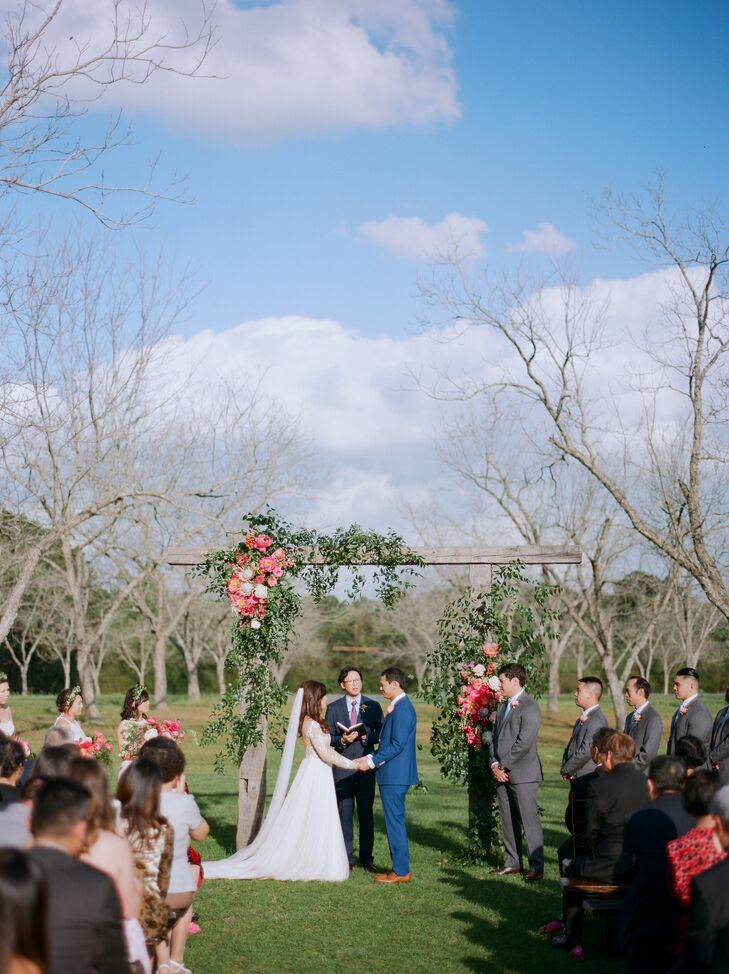 Deborah and Elton chose Chandelier Grove in Tomball, Texas, the site of the ceremony and reception, for its Southern charm. The couple said their vows under a flower arch amid blossoming bluebonnets in a pecan grove.