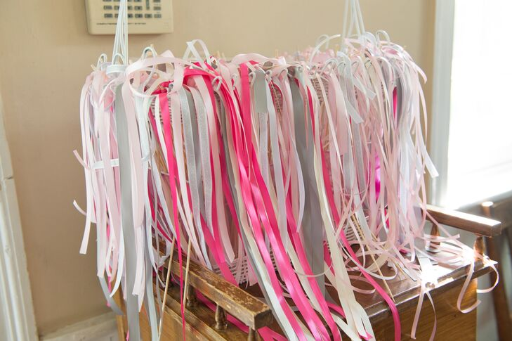 As the newlyweds made their exit from the ceremony, their family and friends waved festive pink and purple ribbons wands instead of tossing grains of rice.