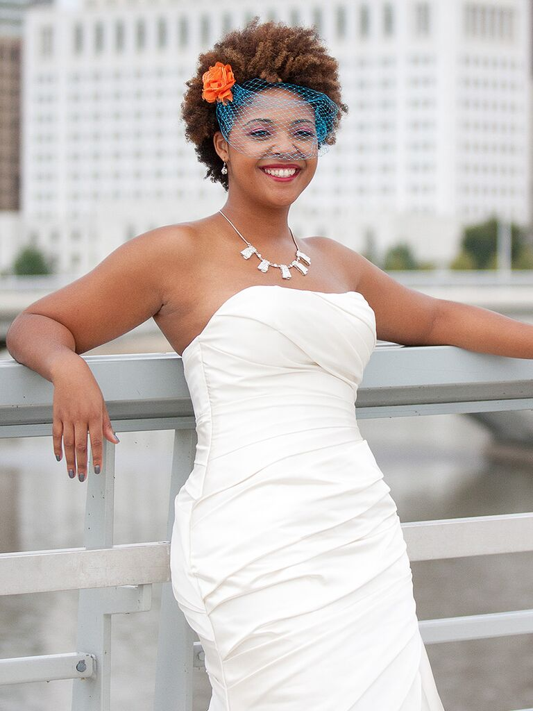 Short curly wedding hairstyle with a bright blue birdcage veil