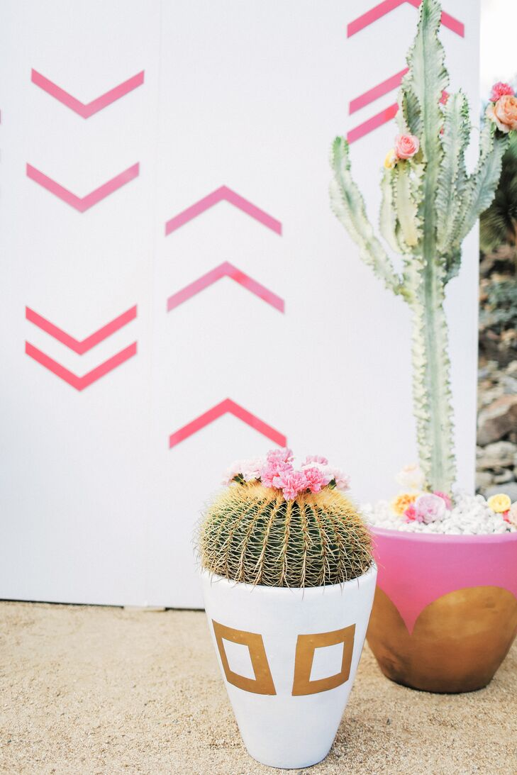 While exchanging vows, Katie and Brian (who are avid bikers) stood before potted cactus topped with rose blossoms, and a white wood panel backdrop painted with pink sharrows, often seen on streets to mark the bike lane.