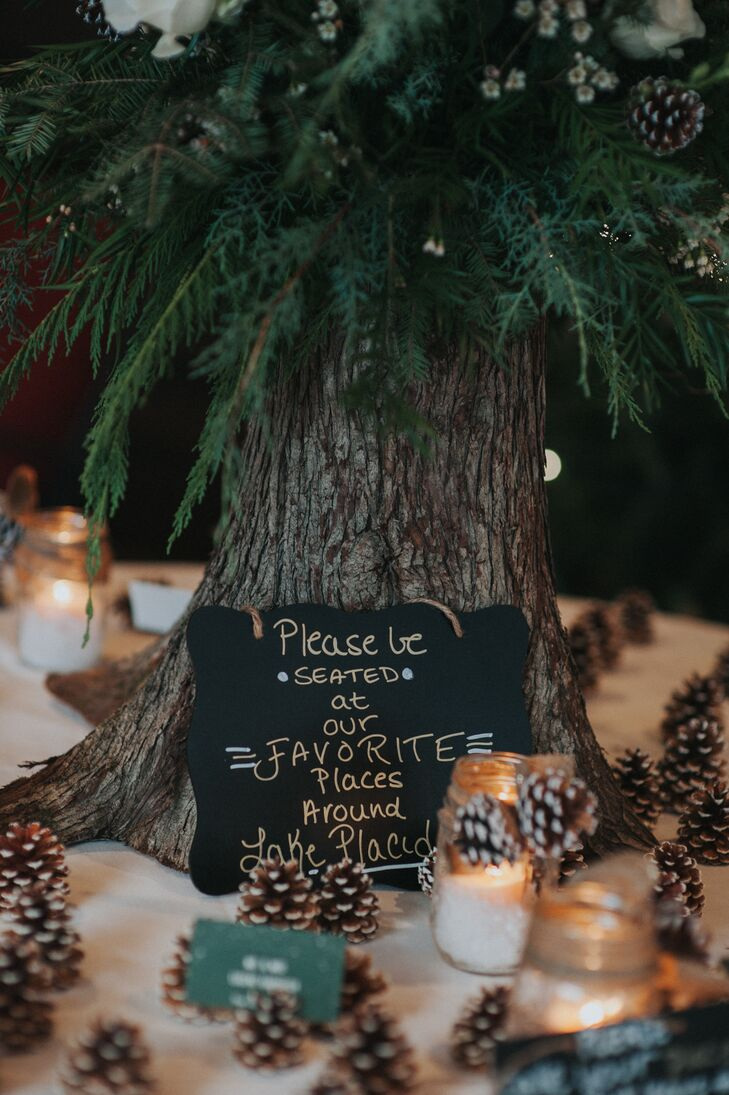 A chalkboard sign leaned against a faux pine tree trunk asked guests to find their seats.