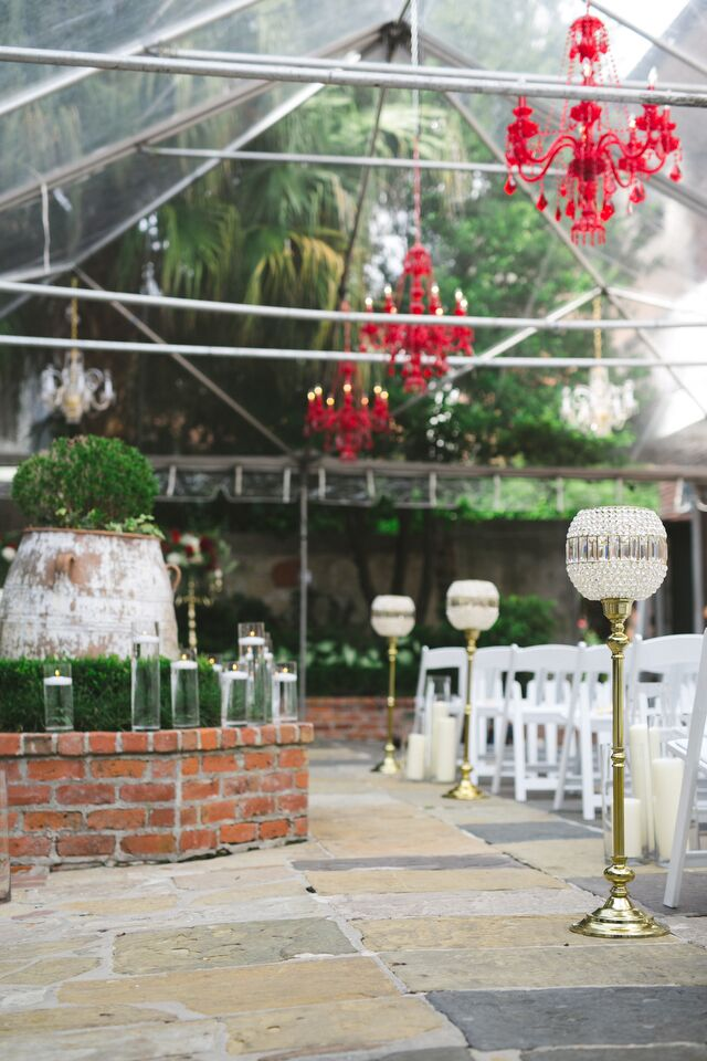 For the courtyard ceremony, a clear tent was decorated with white chairs and strung with red chandeliers.