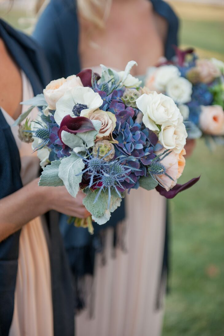 Flora Fauna Designs brought the drama when it came to the bridesmaid bouquets, creating textured arrangements of hydrangeas, ranunculus, dahlias, thistles, cotton and a variety of roses in shades of vibrant plum, steel blue, silver, blush, pink, white and green. The autumnal tones of the arrangements popped against the blush bridesmaid gowns, while complementing their navy pashmina shawls.