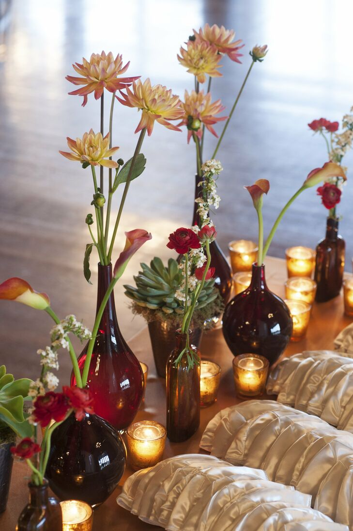 Yarmulkes sat on a table decorated with votive candles and red glass vases filled with golden saffron dahlias, flame calla lilies and red ranunculus.