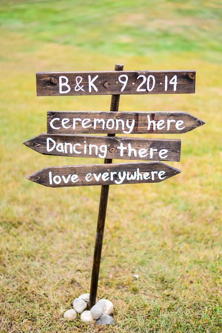 The groom created many woodwork details for the wedding. He diligently stained and distressed a wooden sign to direct guests around the grounds, in addition to burning 'Mr.' and 'Mrs.' into wooden slabs for the back of the couple's chairs and hand cutting and burning small branches used to hold name tags.