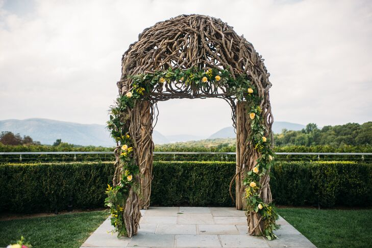Wispy green and yellow seasonal flowers were intertwined in the branches of The Garrison's wedding arch to enhance the rustic look.