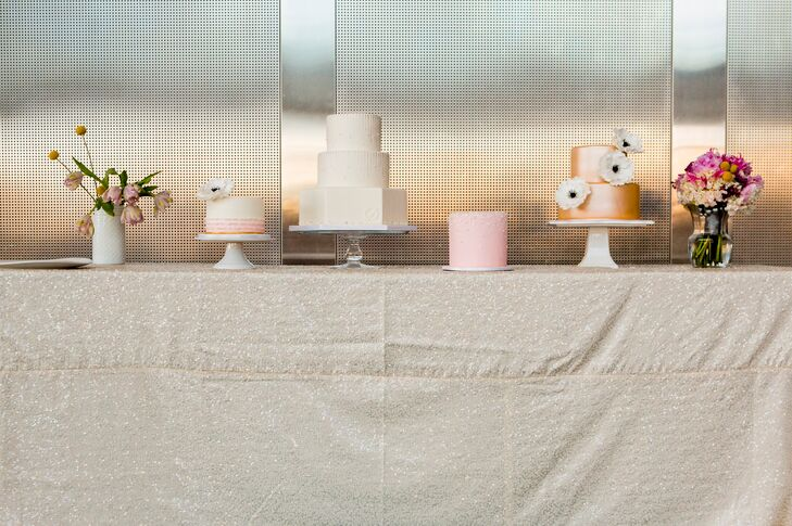 Instead of having just one wedding cake, the bride and groom had four! They designed a unique cake bar with pink and ivory tiered cakes with mismatched fondant designs to match their color theme.