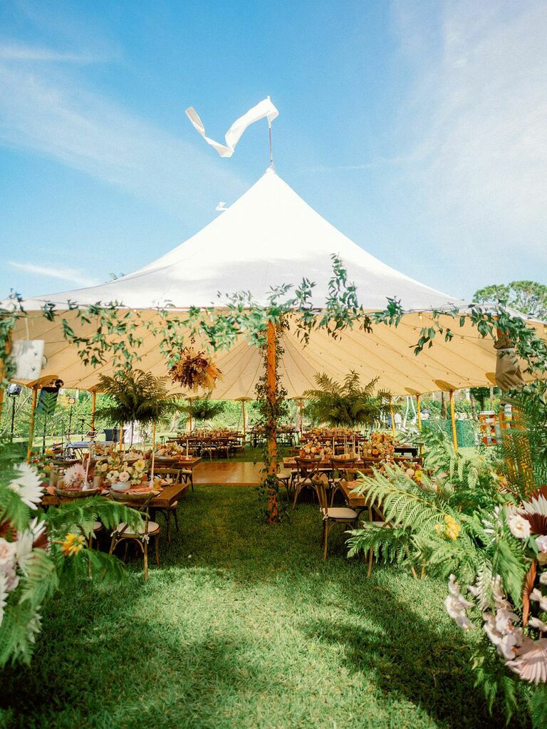 Statement wedding sailcloth tent entrance with lush florals and greenery