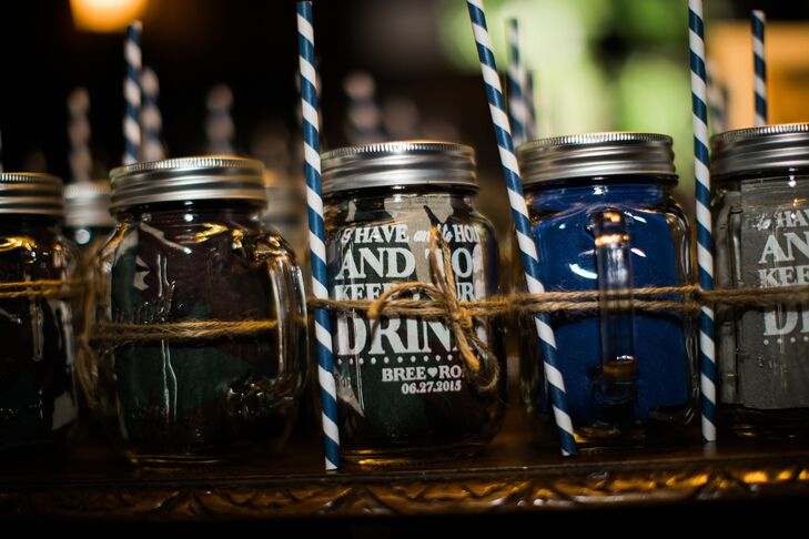 "Keeping with the wedding's rustic theme, Aubrey and Robert gave each guest a customized mason jar for them to use during cocktail hour, a striped paper straw and a personalized koozie with the wedding's wedding date, the couple's names and sayings like ""To have and to hold and to keep your drink cold."""