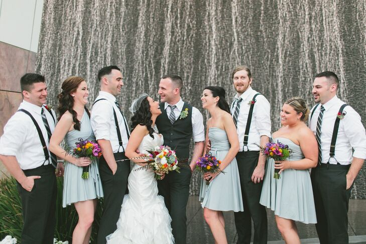 Kaitlyn and Seth shared a picture-worthy moment with their wedding party, who followed the neutral part of the day's palette. The groomsmen wore charcoal pants and suspenders with white dress shirts, while the bridesmaids wore short, light gray dresses in different styles for the most comfortable experience possible.