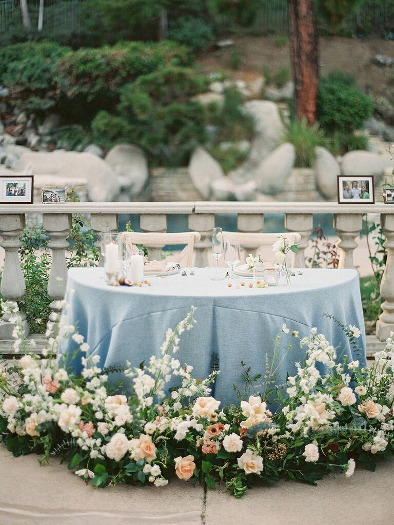 Sweetheart table with blue linens and clusters of fresh flowers