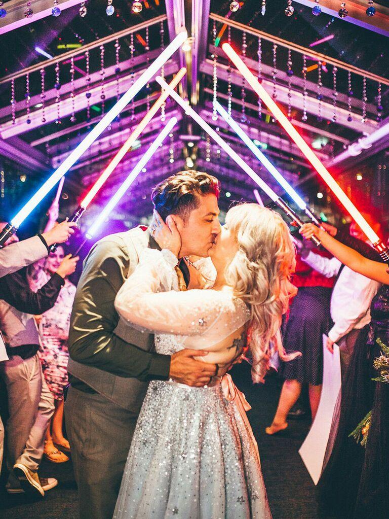 Bride and groom under Star Wars light saber arch
