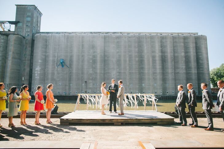 """We had a true 'Buffalo' style wedding—industrial chic style with Buffa-love everywhere!""says Bernice. The outdoor wedding ceremony took place alongside the Buffalo River surrounded by a cluster of incredible old grain elevators called ""Silo City"" which recently because an event venue. ""They'd actually never had a wedding there, but we knew we had to be the first!"" she adds."