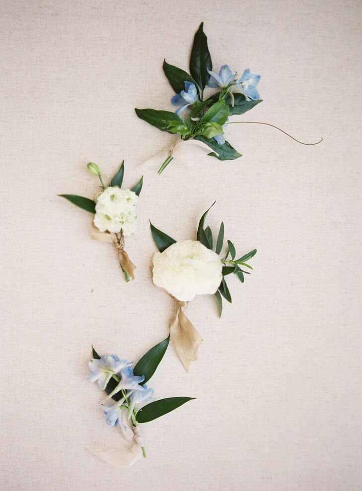 Fresh-flower boutonnieres were made with ivory blooms and blue blossoms, which complemented the bridesmaid dresses.