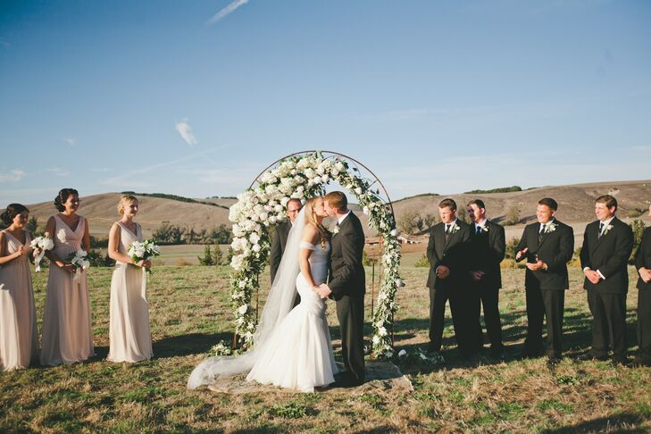 Lydia and Brandon shared their first kiss in front of the wedding arch draped with an overflowing arrangement of white peonies mixed with greens—a romantic decoration for a romantic occasion.
