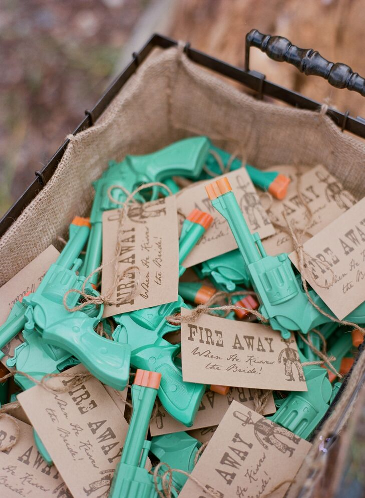"""Chutney and Steve had green toy guns tied with kraft paper that said, """"Fire away when he kisses the bride!"""" Guests shot the guns into the air during the first kiss, and used them as photo props during the reception."""