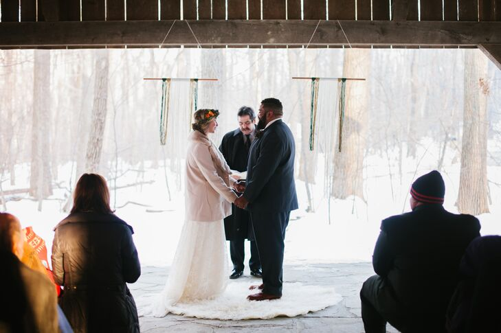 Two yarn macrame decorations hung from the ceiling of the wooden pavilion, which served as the backdrop at the ceremony. Paula and Nik stood on a white soft rug, adding a nice cozy detail to the wintry space.