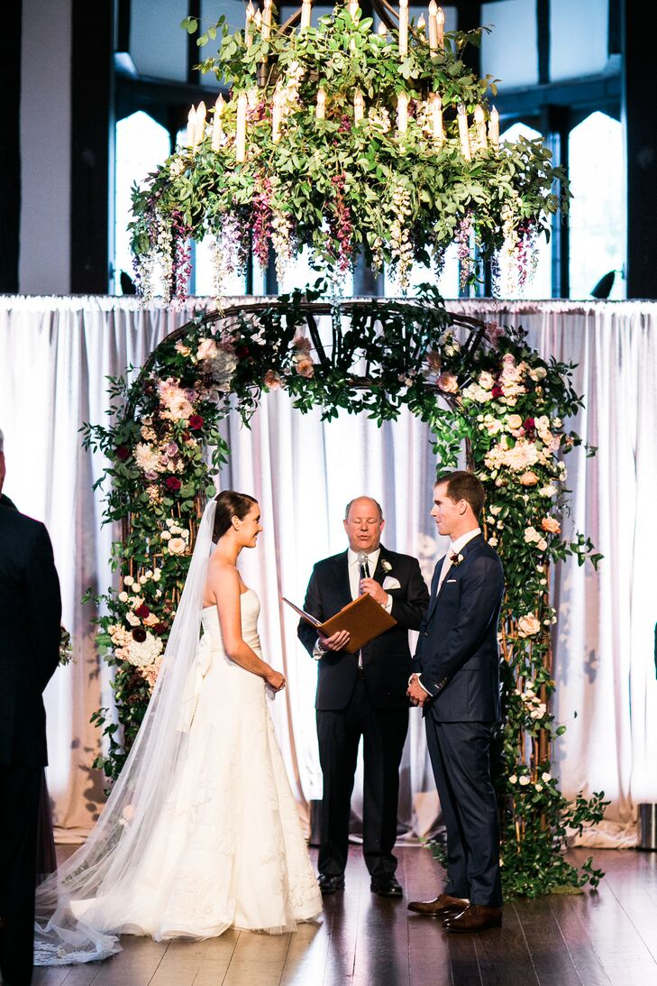 Couple Under Oversized Floral Chandelier and Wedding Arch