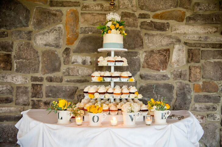 "The tall stand displayed a variety of cupcakes, with the white wedding cake with a light blue band wrapped around the bottom of the perched top. The cake had yellow and ivory blooms that matched the flowers inside the vintage-styled mugs spelling out ""love."""