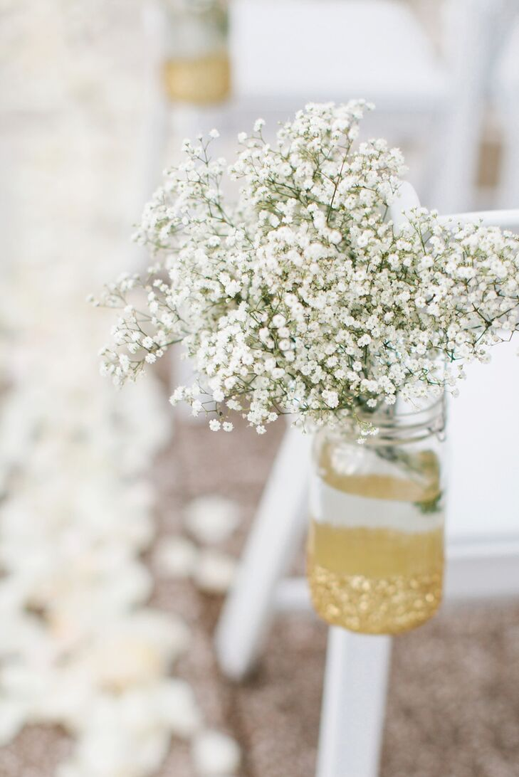 During the outdoor ceremony, every other chair lining the aisle was decorated with a mason jar of baby's breath flowers.