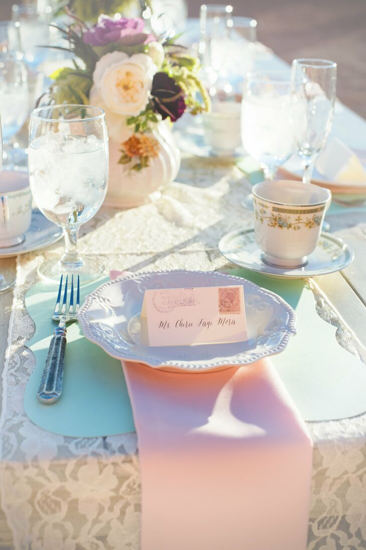 Warm pink and cool mint green linens added lovely contrast to the desert's red rocks. Vintage plates and postcard-themed place cards added to the day's travel theme.