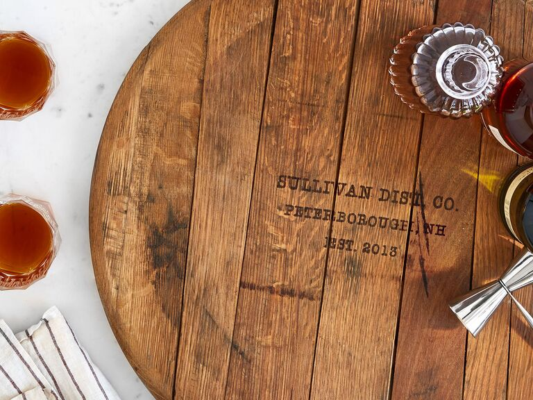 Rustic reclaimed wood round serving board personalized with couple's surname