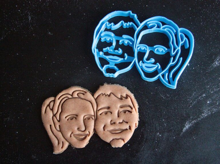 Custom cookie cutter of a couple's faces pictured with cookie dough example