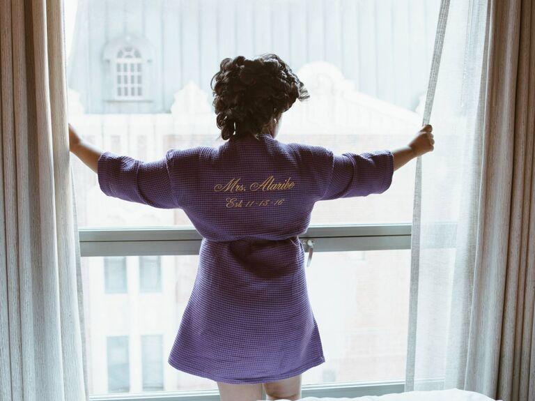 Bride wearing robe looking out window